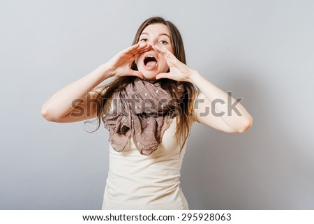 Young woman calling someone with hands around his mouth. On a gray background. - stock photo