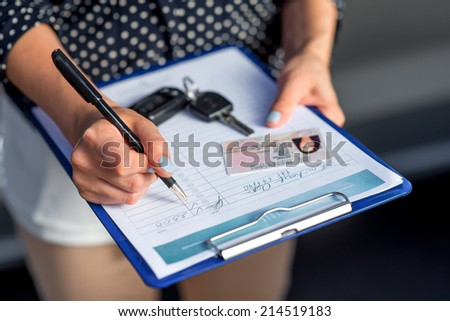Young woman car rental inspector filling contract  - stock photo