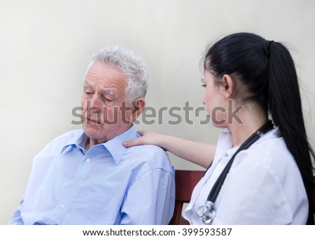 Young woman caregiver listening and comforting senior man on the bench - stock photo