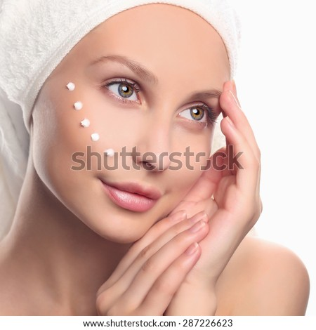 young woman cares for face skin.beautiful girl with cosmetic cream on a clean fresh face. Skin care concept - stock photo