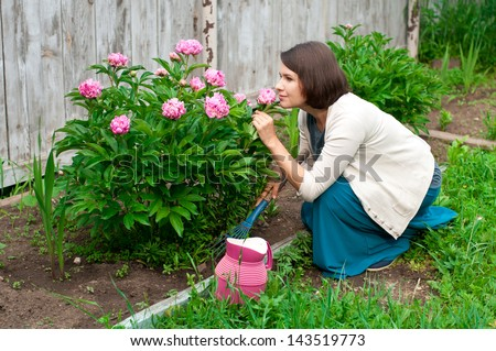 young woman caring for flowers in the garden - stock photo