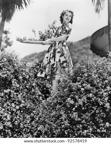 Young woman carrying a tray of Flowers in a garden - stock photo
