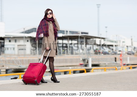 Young woman carrying luggage. - stock photo