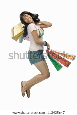 Young woman carrying shopping bags and jumping - stock photo