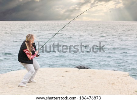 Young woman catching fish. - stock photo