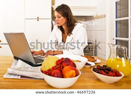 Young woman, catching up with the day's events on her laptop whilst drinking a glass of orange juice - stock photo
