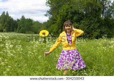 Young woman, Caucasian, brunette, with sunflower in park. - stock photo