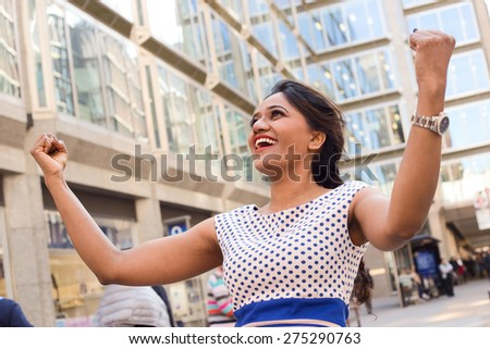 young woman celebrating in the street - stock photo
