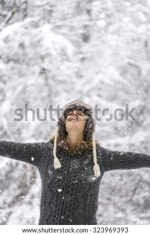 Young woman celebrating winter with her arms spread widely looking up towards the sky while gentle snowflakes fall on her. - stock photo