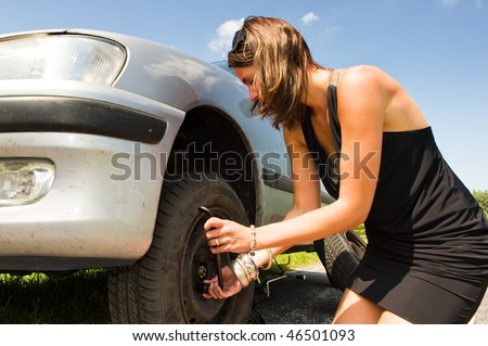 Young woman changing a flat tire on her car - stock photo