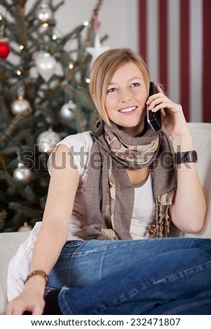 Young woman chatting to friends at Christmas on her mobile phone relaxing on a sofa in front of the Christmas tree - stock photo