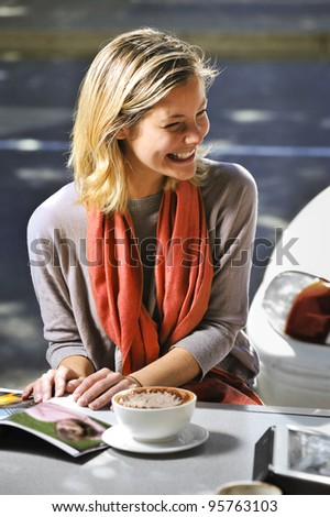 young woman chatting with a friend in a cafe - stock photo