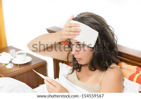 Young woman checking her temperature - stock photo