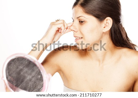 young woman checks her nose in the mirror - stock photo