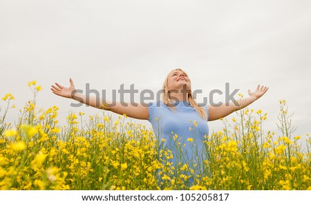 young woman cheering in the rape field - stock photo