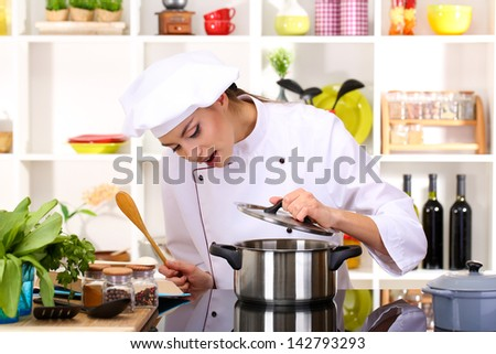 Young woman chef cooking in kitchen - stock photo