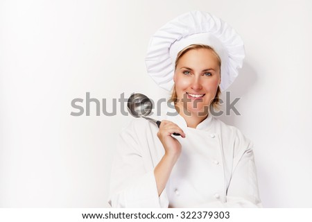 Young woman chef holding ladle, smiling. - stock photo