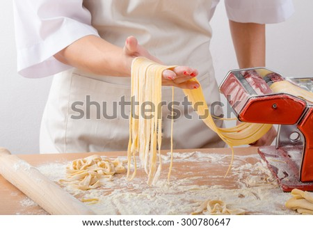 Young woman chef prepares homemade pasta from durum semolina flour - stock photo