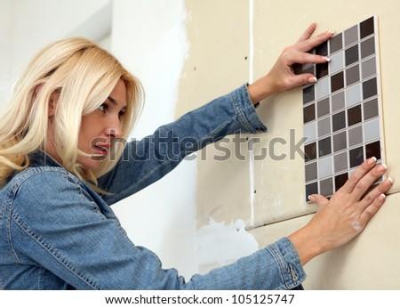 Young woman choose tiles - stock photo