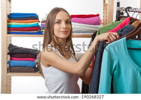 young woman chooses clothes, isolated on white background - stock photo