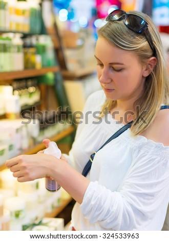 Young woman choosing cosmetic cream in beauty shop. - stock photo