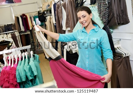 Young woman choosing drerss during garments clothing shopping at store - stock photo