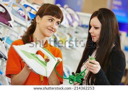 Young woman choosing electric iron in home appliance shopping mall supermarket - stock photo