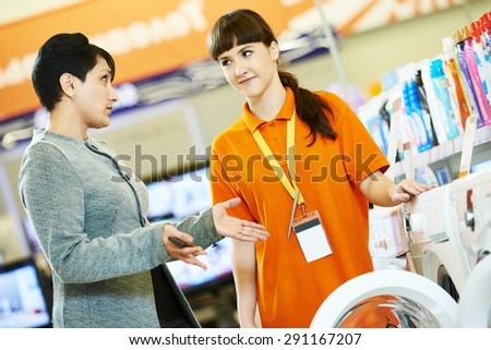 Young woman choosing electric kitchen blender in home appliance shopping mall supermarket - stock photo