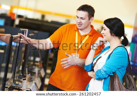 Young woman choosing tv set with shop assistant in home appliance shopping mall supermarket - stock photo