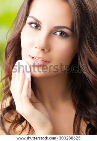 young woman cleaning skin by cotton pad - stock photo