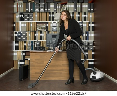 Young woman cleaning the office - stock photo