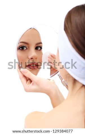 Young woman cleansing her face, isolated on white - stock photo