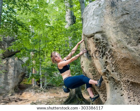 Young woman climbing on large boulder outdoor summer day - stock photo