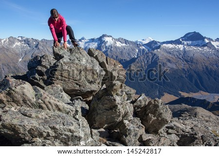 Young woman climbing rocky mountain ridge - stock photo