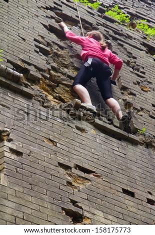 Young woman climbing up a brick wall - stock photo