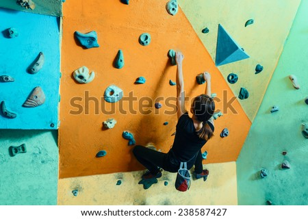 Young woman climbing up on wall in gym, rear view - stock photo