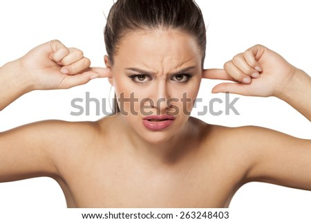 young woman closes her ears because of the noise - stock photo