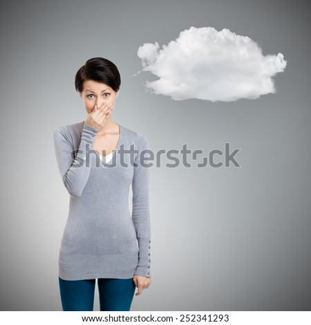 Young woman closes her nose with hand, isolated on grey background with cloud - stock photo