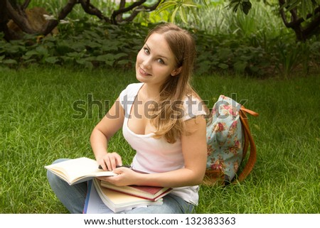 Young woman college student with book and bag studing in a park - stock photo