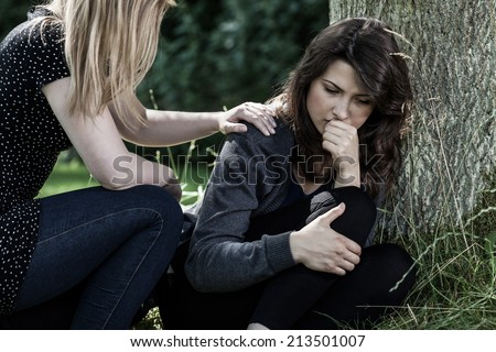 Young woman comforting her mourning friend - stock photo