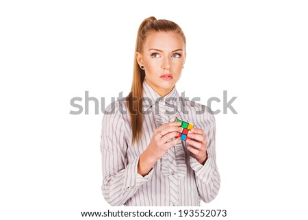 young woman concentrated solving the Rubik's Cube - stock photo