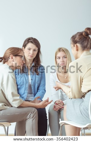 Young woman confiding problem to her support group - stock photo