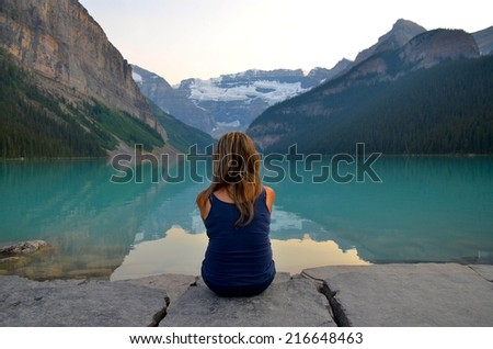 Young woman contemplating at Lake Louise, Canada - stock photo
