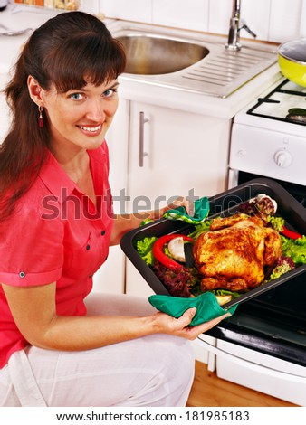 Young woman cooking chicken at kitchen. - stock photo