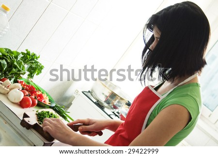 Young woman cooking healthy food with lots of vegetables - stock photo