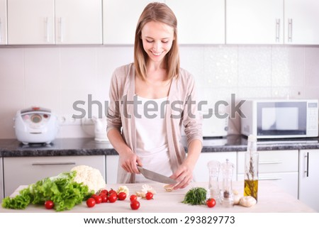 Young Woman Cooking in the kitchen.  Dieting vegetarian concept. Healthy Lifestyle. Cooking At Home. Prepare Food - stock photo