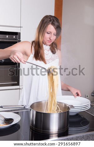 young woman cooking spaghetti bolognese - stock photo