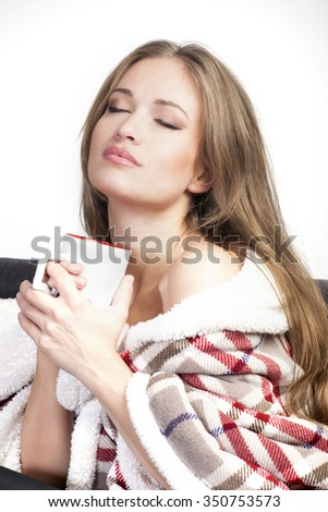 young woman covered with warm blanket enjoy in cup of tea or coffee - stock photo