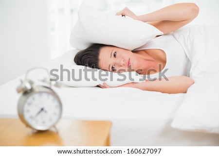 Young woman covering ears with pillow in bed and alarm clock on side table - stock photo