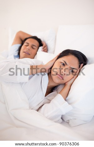 Young woman covering her ears to block her boyfriends snoring - stock photo